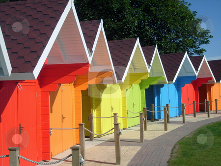 Bright colored seaside chalets stock photo, Row of brightly colored seaside chalet buildings. by Martin Crowdy