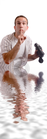 Chest Deep stock photo, A young man standing chest deep in some water, while holding a set of binoculars by Richard Nelson