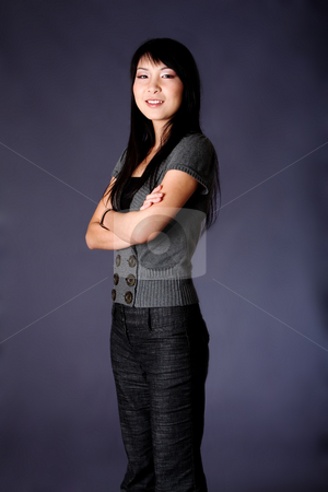 Asian business woman stock photo, Beautiful Asian American business career woman standing in grey casual clothes with arms crossed, isolated. by Paul Hakimata