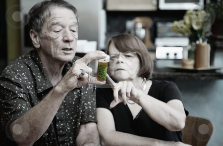Couple at Home with Medication stock photo, Couple at Home Considering Medication in Bottle by Scott Griessel