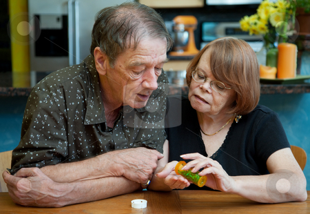 Senior Couple at Home Discussing Medication stock photo, Senior Couple at Home in Kitchen Discussing Medication by Scott Griessel