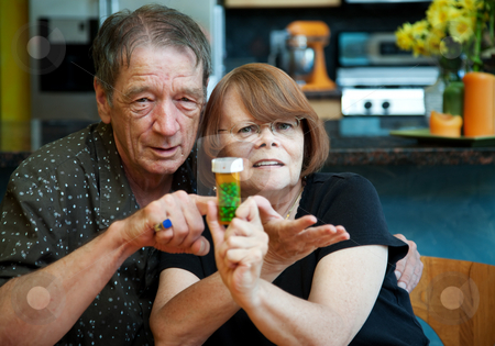 Senior Couple at Home with Prescription stock photo, Senior couple at home with prescription bottle by Scott Griessel