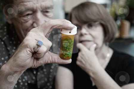 Senior Couple at Home with Perscription stock photo, Senior couple at home with prescription bottle, focus by Scott Griessel
