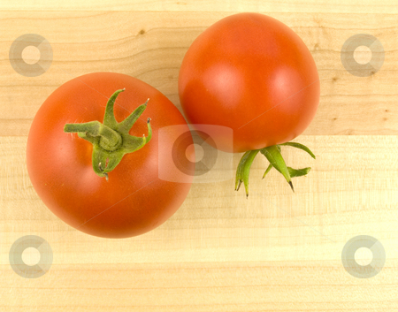 Two Tomatoes on wooden background stock photo, Two ripe tomatoes on a wooden background by John Teeter