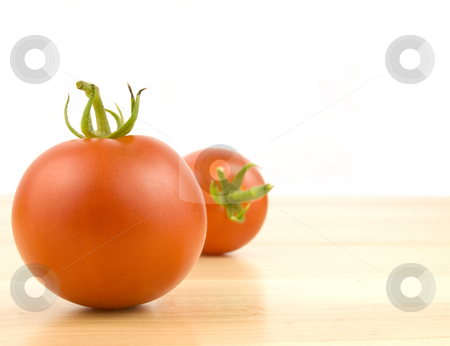 Two tomatoes stock photo, Two Tomatoes on wood with a white background by John Teeter