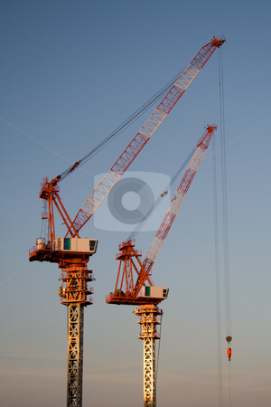 Construction Cranes stock photo, Two cranes used for skyscraper construction at sunset by Holger Feroudj