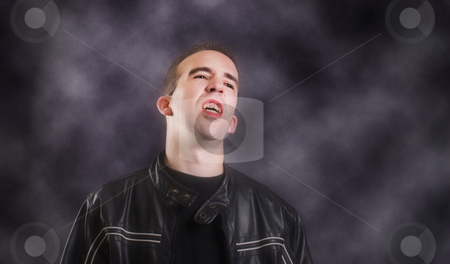 Vampire stock photo, A modern day vampire showing his teeth, while standing in a dark foggy room by Richard Nelson