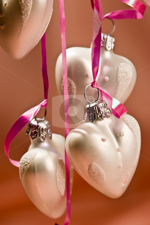 Christmas ball stock photo, Holiday series: some white christmas heart-shaped ball over light red background by Gennady Kravetsky
