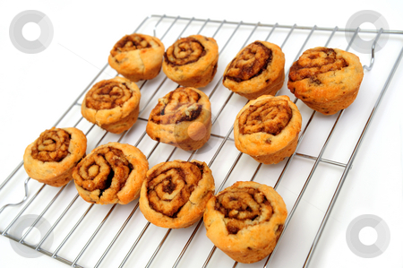 Mini Cinnamon Rolls stock photo, Small cinnamon rolls cooling a silver metal rack after baking in the oven by Lynn Bendickson