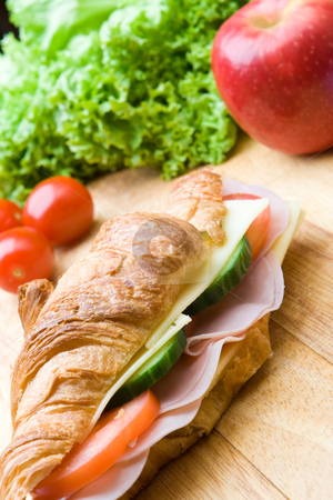 Fresh croissant with ham, cheese and salad stock photo, Fresh croissant with ham, cheese, salad and a red apple by Robert Anthony