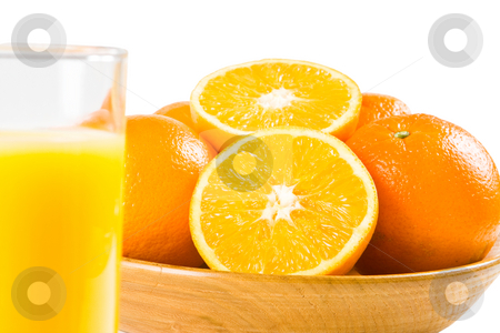 Oranges with a glass of orange juice in the foreground stock photo, Two halves of orange in a wooden bowl with uncut oranges and a glass of orange juice in the foreground by Robert Anthony