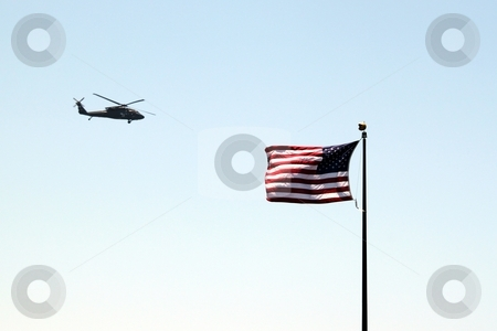 Usa flag helicopter stock photo, USA helicopter flying by a US flag with blue sky by Henrik Lehnerer