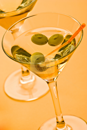 Martini stock photo, Two bocal of martini with olive over yellow by Gennady Kravetsky