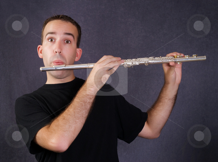 Man Playing Flute stock photo, A young man playing a metal flute which is a wind instrument by Richard Nelson