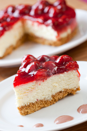 Slice of delicious strawberry cheese cake stock photo, Slice of delicious strawberry cheese cake with a cake in the background by Robert Anthony