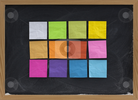 Colorful sticky notes on blackboard stock photo, A dozen of blank, colorful sticky notes on a blackboard with white chalk smudges by Marek Uliasz