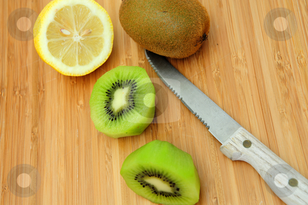 Sliced Kiwi And Lemon stock photo, Kiwi fruit peeled and sliced in half with a lemon and knife by Lynn Bendickson