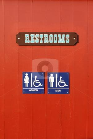 Restroom stock photo, Blue woman man handicapped restroom sign on red wall by Henrik Lehnerer
