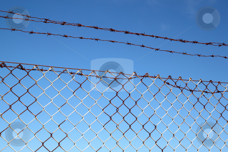 Rusty old barbed wire security fence and blue sky. stock photo, Rusty old barbed wire security fence and blue sky. by Stephen Rees
