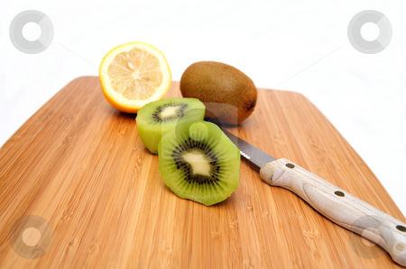 Kiwi And Lemon stock photo, Kiwi fruit peeled and sliced in half with a lemon and knife on a bamboo cutting board by Lynn Bendickson