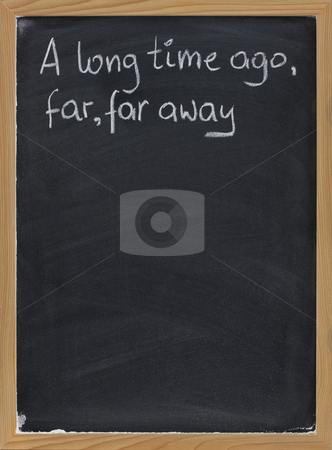 Opening phrase of storytelling or fairytale stock photo, A long time ago, far, far away - a phrase for opening oral narratives, story or fairytale handwritten with white chalk on blackboard, copy space below by Marek Uliasz