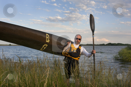 Paddler carrying a racing kayak with number thirteen stock photo, Mature paddler carrying his long racing kayak on a grassy lake shore in northern Colorado, thirteen - temporary race number placed on deck by myself by Marek Uliasz