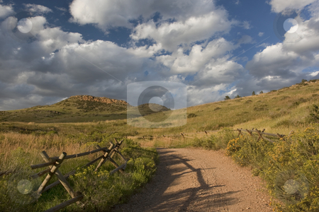 Dirt road in Colorado at foothills of Rocky Mountains  stock photo, Dirt road and wooden fence at foothills of Rocky Mountains near Fort Collins, Colorado, late summer by Marek Uliasz