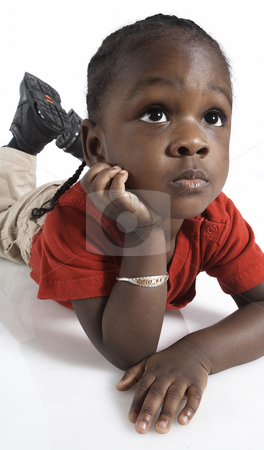 Young african american boy stock photo, Young African American boy lays on stomach, rests chin on hand, looks up, full body by Alex Cao
