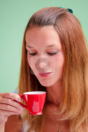 Redhead drinking coffee stock photo, Redhead woman drinking coffee from a red cup by Natalia Macheda