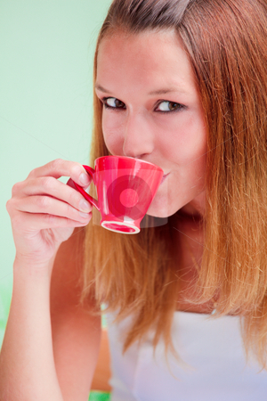 Redhead woman drinking coffee stock photo, Redhead young woman drinking coffee from red cup by Natalia Macheda