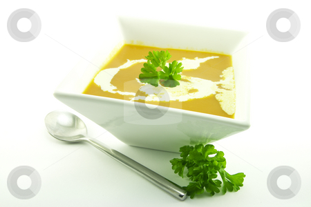 Tomato Soup in a Black Bowl stock photo, Rich red hot tomato soup in a small square bowl with a sprig of parsley, cream and a spoon on a white background by Keith Wilson