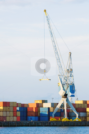 Large Cargo Crane and Containers at Seaport stock photo, A large cargo crane stands at port in front of stacks of containers. There is no one viewable in the image. Vertically framed shot. by Corepics VOF