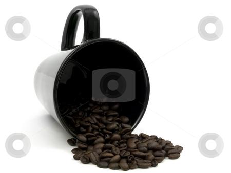 Black mug spilling coffee beans stock photo, Black mug spilling coffee beans on a white background by John Teeter