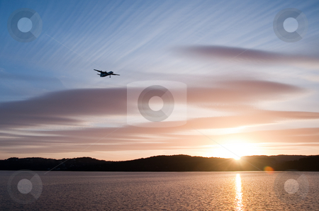 Sunset flying #2 stock photo, Airplane in the sunset over the water with blue sky and hills in the background by Thomas ??derud