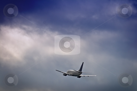Jet airliner against stormy sky stock photo, Jet airliner against stormy sky by Interlight