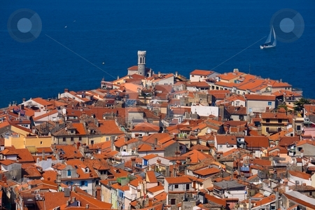 Piran, Slovenia stock photo, Roofs of a typical southern European town and a sailboat by Interlight