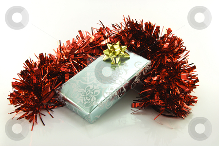 Silver Wrapped Gift with Tinsel stock photo, Single shiny silver wrapped gift with gold bow and red tinsel on reflective white background by Keith Wilson
