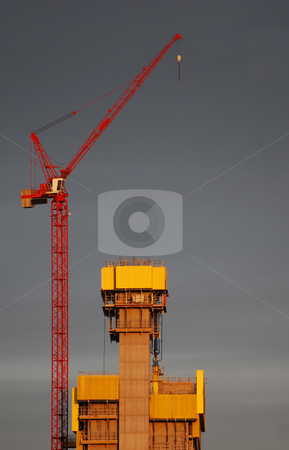 The Crane stock photo, Yellow and red crane naturally lit with rear sunset against dull sky by Paul Inkles