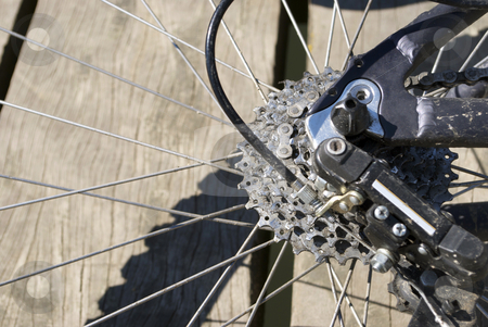 Bike Cog stock photo, Royalty Free Stock Image of The Cogs of a Mountain Bikes Rear Wheel against wood background, providing copyspace to the left by Paul Inkles