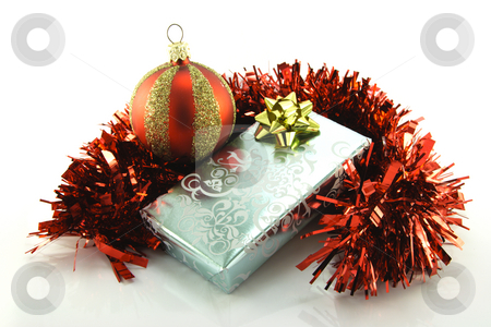 Silver Gift with Tinsel and Bauble stock photo, Single shiny silver wrapped gift with gold bow, red tinsel and green holly on a reflective white background by Keith Wilson
