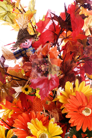Fall Flowers stock photo, Closeup view of some fake fall flowers and leaves along with a small scarecrow, isolated against a white background by Richard Nelson