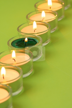 Tea lights in a row stock photo, Tea lights in a row with a green one in the row by Arnold Barna