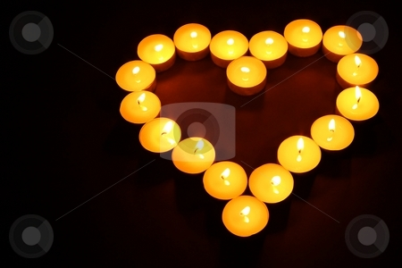 Heart made of tea lights stock photo, Heart made of tea lights in dark high angle view by Arnold Barna