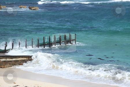 Pier choppy seas stock photo, Wooden pier on beach with choppy blue seas by Kheng Guan Toh