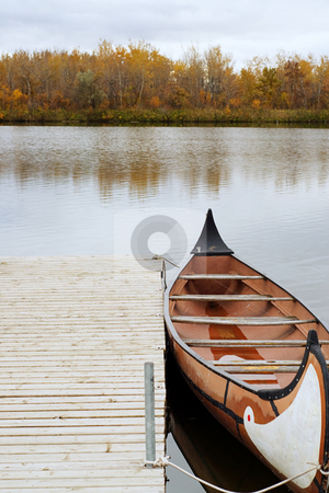 Canoe stock photo, A canoe docked and floating on the river, shot on a cloudy day by Richard Nelson