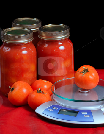 Jars of Tomatoes stock photo, Jars of canned tomatoes situated beside some fresh tomatoes and a kitchen scale by Richard Nelson
