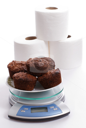 Bran Muffins and Toilet Paper stock photo, A plate of bran muffins on a kitchen scale with 3 rolls of toilet paper by Richard Nelson