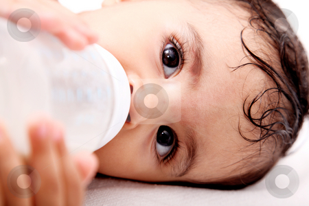Baby and bottle stock photo, Baby drinking milk of her bottle. White background by Giuseppe Ramos