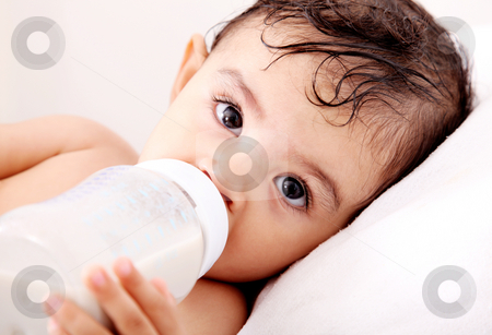 Baby milk stock photo, Baby drinking milk of her bottle. White background by Giuseppe Ramos