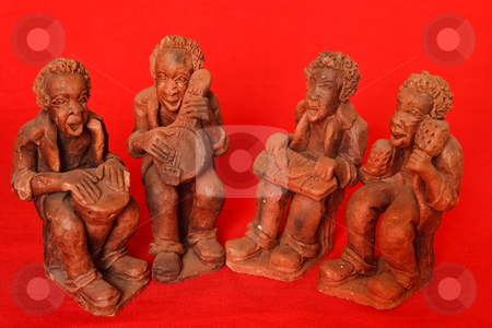 African Quartet stock photo, A quartet of clay hand made African musicians on a red background by Ian Genis